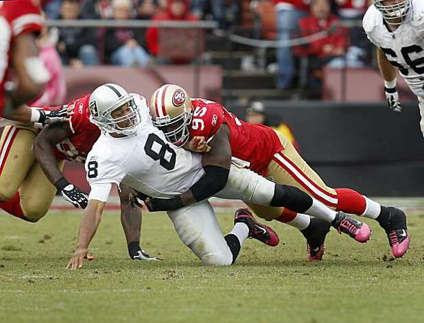 Jason Campbell of the Raiders is brought down by Ricky Jean Francois in the second half Sunday at Candlestick Park. Photo: Brant Ward, The Chronicle