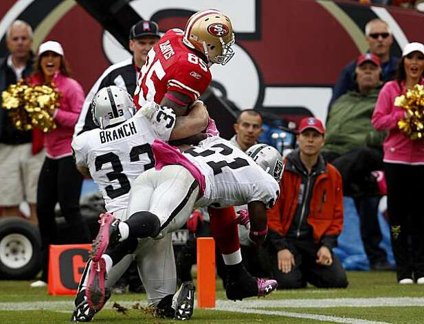 The 49ers' Vernon Davis is dragged down by two Raiders defenders in the fourth quarter Sunday at Candlestick Park. Photo: Brant Ward, The Chronicle