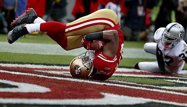 Michael Crabtree rolls in the endzone after his touchdown, which put the 49ers ahead for good, as defender Tyvon Branch watches Sunday at Candlestick Park. Photo: Brant Ward, The Chronicle