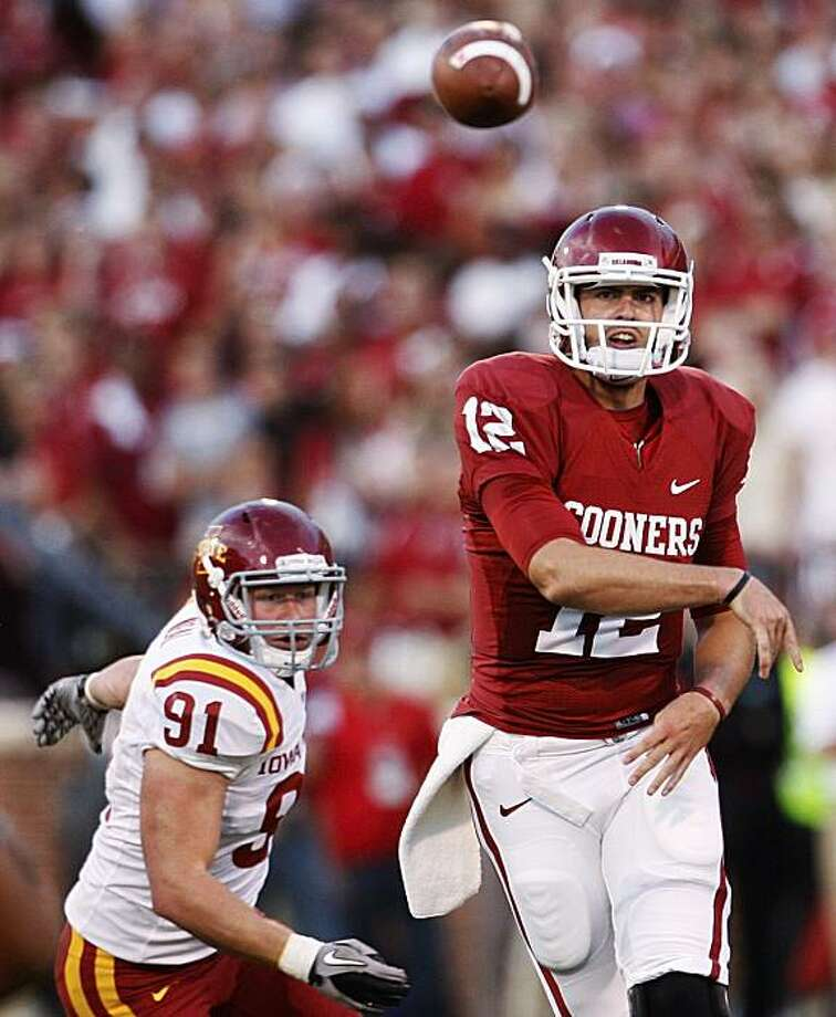 Oklahoma quarterback Landry Jones, right, and Iowa State Patrick Neal, left, watch his pass in the first quarter of an NCAA college football game in Norman, Okla., Saturday, Oct. 16, 2010. Oklahoma won 52-0. Photo: Sue Ogrocki, AP