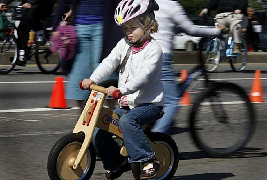 "Louisa Romero, 5, takes advantage of the Bicycle Coalition's area to ""ride without training wheels"" near Broadway at San Francisco's first Sunday Streets event of the year, which shut down the Embarcadero from the AT&T Park to Pier 45. Photo: Brant Ward, The Chronicle"
