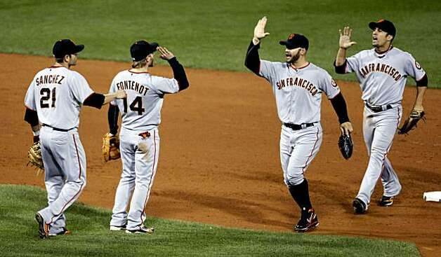 Giants infielders Freddy Sanchez and Mike Fontenot greet outfielders Cody Ross and Andres Torres after the Giants defeated the Philadelphia Phillies in Game 1 of the NLCS at Citizens Bank Park in Philadelphia on Saturday. Photo: Lance Iversen, The Chronicle