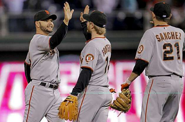 Cody Ross high fives Mike Fontenot and Freddy Sanchez as they celebrate the Giants' win over the Philadelphia Phillies in Game 1 of the National League Championship Series on Saturday at Citizens Bank Park in Philadelphia. Photo: Michael Macor, The Chronicle