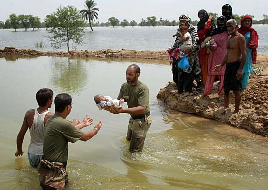 Pakistan army soldiers pass a baby across a water course as they help people flee from their flooded village following heavy monsoon rains in Taunsa near Multan, Pakistan, on Sunday, Aug. 1, 2010.  The death toll from massive floods in northwestern Pakistan rose to 1,100 Sunday as rescue workers struggled to save more than 27,000 people still trapped by the raging water. Photo: Khalid Tanveer, AP