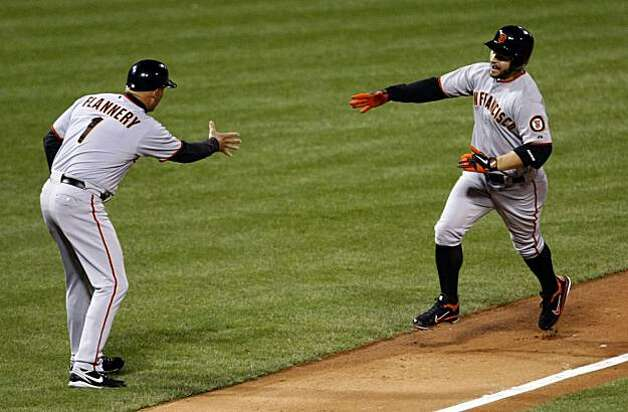 San Francisco Giants third base coach Tim Flannery reaches out to greet Cody Ross after Ross hit a solo home run in the third inning of Game 1 of the NLCS at Citizens Bank Park in Philadelphia on Saturday. Photo: Lance Iversen, The Chronicle