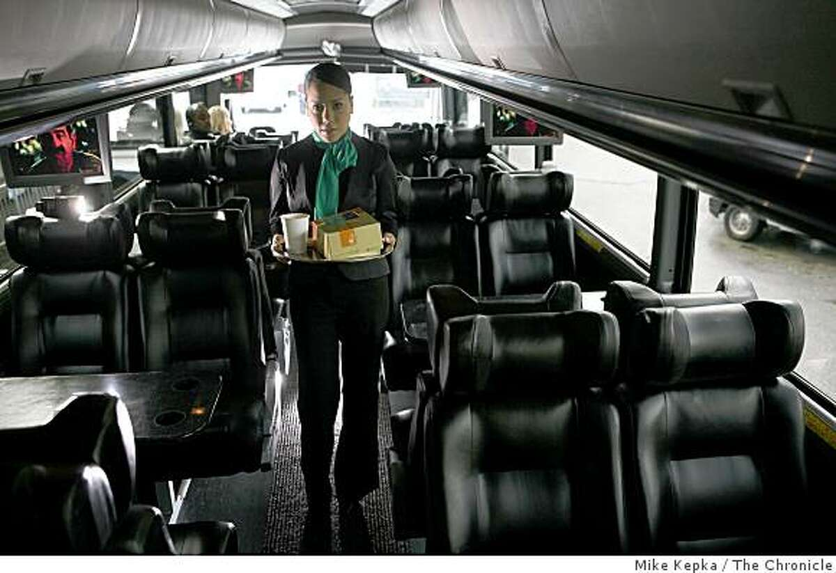 Inside a new Wi-Drive shuttle, presented by Bauer's IT, Arlene Martinez, a Ride Host, stands for a portait with coffee and custom breakfasts from Specialty�s Caf? & Bakery on Thursday Feb. 27, 2009 at his company headquarters in San Francisco, Calif.