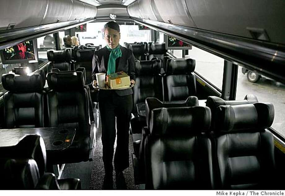Inside a new Wi-Drive shuttle, presented by Bauer's IT, Arlene Martinez, a Ride Host,  stands for a portait with coffee and custom breakfasts from Specialty�s Caf? & Bakery on Thursday Feb. 27, 2009 at his company headquarters in San Francisco, Calif. Photo: Mike Kepka, The Chronicle
