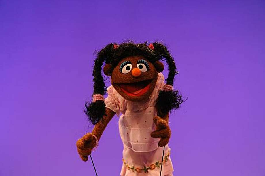 "In this publicity image released by Sesame Street, a brown muppet representing an African-American girl is shown during the taping of the ""I Love My Hair,"" video for the children's program, ""Sesame Street."" The video was inspired by the five-year-old daughter of ""Sesame Street"" head writer Joey Mazzarino. Photo: Zach Hyman, AP"