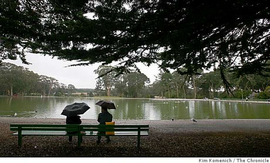 An umbrella carrying couple sits on a bench at Spreckels Lake in Golden Gate Park on February 20, 2008 as a weather front moved in, bringing rain and colder temperatures.Photo by Kim Komenich/San Francisco Chronicle Photo: Kim Komenich, The Chronicle