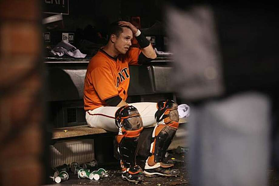 Giants catcher Buster Posey holds his head in the dugout at the end of the 9th inning of the Giants playoff game against the Atlanta Braves on Friday Oct. 7, 2010 in San Francisco, Calif. Photo: Mike Kepka, The Chronicle