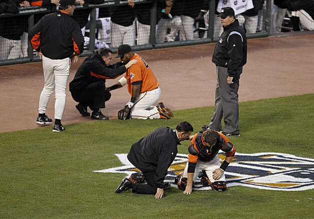 Buster Posey and Pablo Sandoval are checked on by staff after colliding in the first inning as the San Francisco Giants take on the Atlanta Braves  in Game 2 of the National League Division Series at AT&T Park in San Francisco, Calif., on Friday, October 8, 2010. Photo: Paul Chinn, The Chronicle