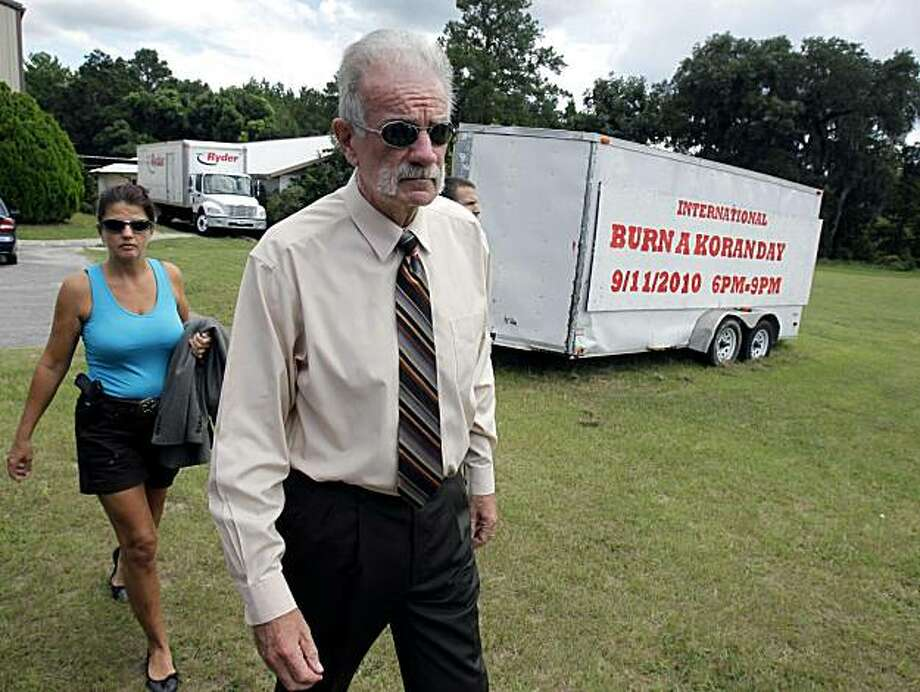 Pastor Terry Jones, right,  of the Dove World Outreach Center arrives at a news conference with an armed escort in Gainesville, Fla., Wednesday, Sept. 8, 2010. Jones stated that he is going forward with a scheduled burning of copies of the Quran at his church on Saturday, Sept. 11. Photo: John Raoux, AP