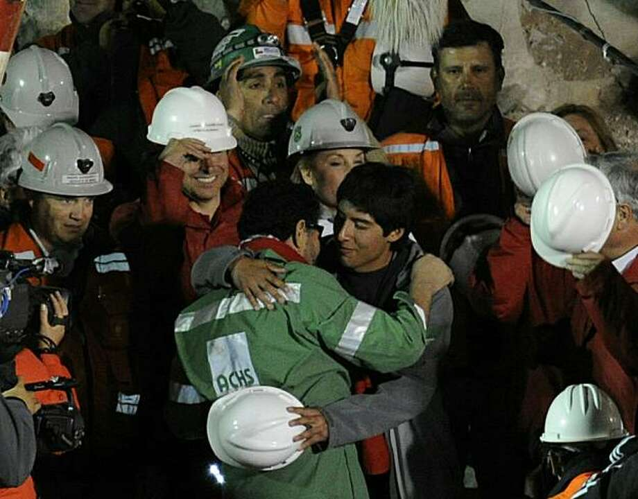 The last of the 33 Chilean miners to be rescued, Luis Urzua (C), embraces a family member after being brought to the surface from the San Jose mine, near Copiapo, Chile on October 13, 2010. The rescue of the 33 miners trapped underground in Chile took some 22 and a half miners, with only the rescue workers left to resurface. Photo: Juan Mabromata, AFP/Getty Images