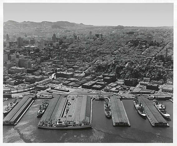 A view of part of the Port of San Francisco's busy waterfront. The ship berthed parallel to the land is at a modern and efficient cargo terminal formed by combining piers 15 and 17.  Photo was taken: 06/11/1963. Photo: Aero Portraits, Port Of San Francisco