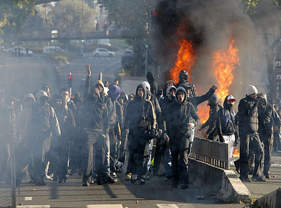 Youth clash with riot police officers, unseen, in Nanterre, outside Paris, Monday Oct.18, 2010. French oil workers are intensifying their fight against President Nicolas Sarkozy's plan to raise the retirement age to 62, a conflict that has hobbled transport and sparked scattered gas shortages. French youth who have rallied to the cause, meanwhile, burned tires or set up blockades outside some schools in Paris and nearby suburbs on Monday. Photo: Jacques Brinon, AP