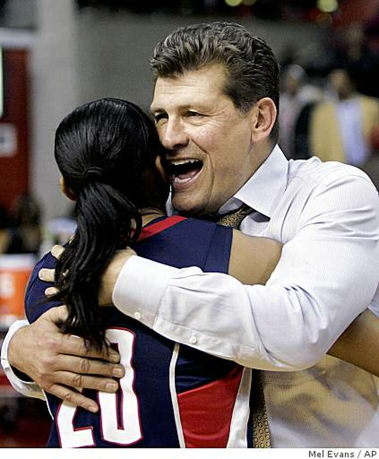 Connecticut head coach Geno Auriemma hugs player Renee Montgomery after defeating Rutgers 69-59 in an NCAA college basketball game Monday, March 2, 2009, in Piscataway, N.J. With the win, Connecticut completed an undefeated (30-0) season.  (AP Photo/Mel Evans) Photo: Mel Evans, AP