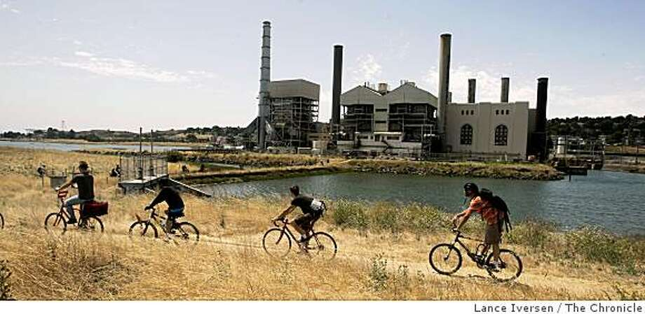 Bikers peddle past an old power plant at Heron's Head Park Saturday. Several hundred bikers and Kayaker's took part in the Imagine The Way tour of the Baytrail between San Francisco's China Basin Park and India Basin Shoreline Park Saturday. The event launched the Blue Greenway Initiative, a 13-mile greenway/waterway network along San Francisco's Southern waterfront. . 6/24/06 Photo: Lance Iversen, The Chronicle