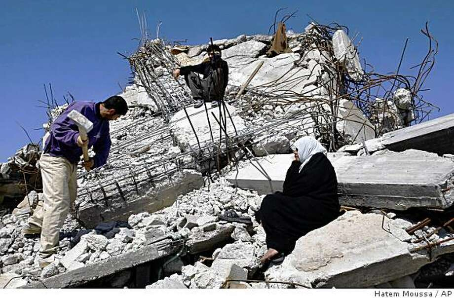 "A Palestinian family works on the rubble of a house destroyed in Israel's latest incursion into Gaza, in Jebaliya, northern Gaza Strip, Tuesday, Feb. 24, 2009. Palestinian Prime Minister Salam Fayyad is asking donor countries to channel hundreds of millions of dollars in expected aid for war-ravaged Gaza ""first and foremost"" through his government, according to his 53-page Gaza reconstruction plan, obtained Thursday by The Associated Press. (AP Photo/Hatem Moussa) Photo: Hatem Moussa, AP"