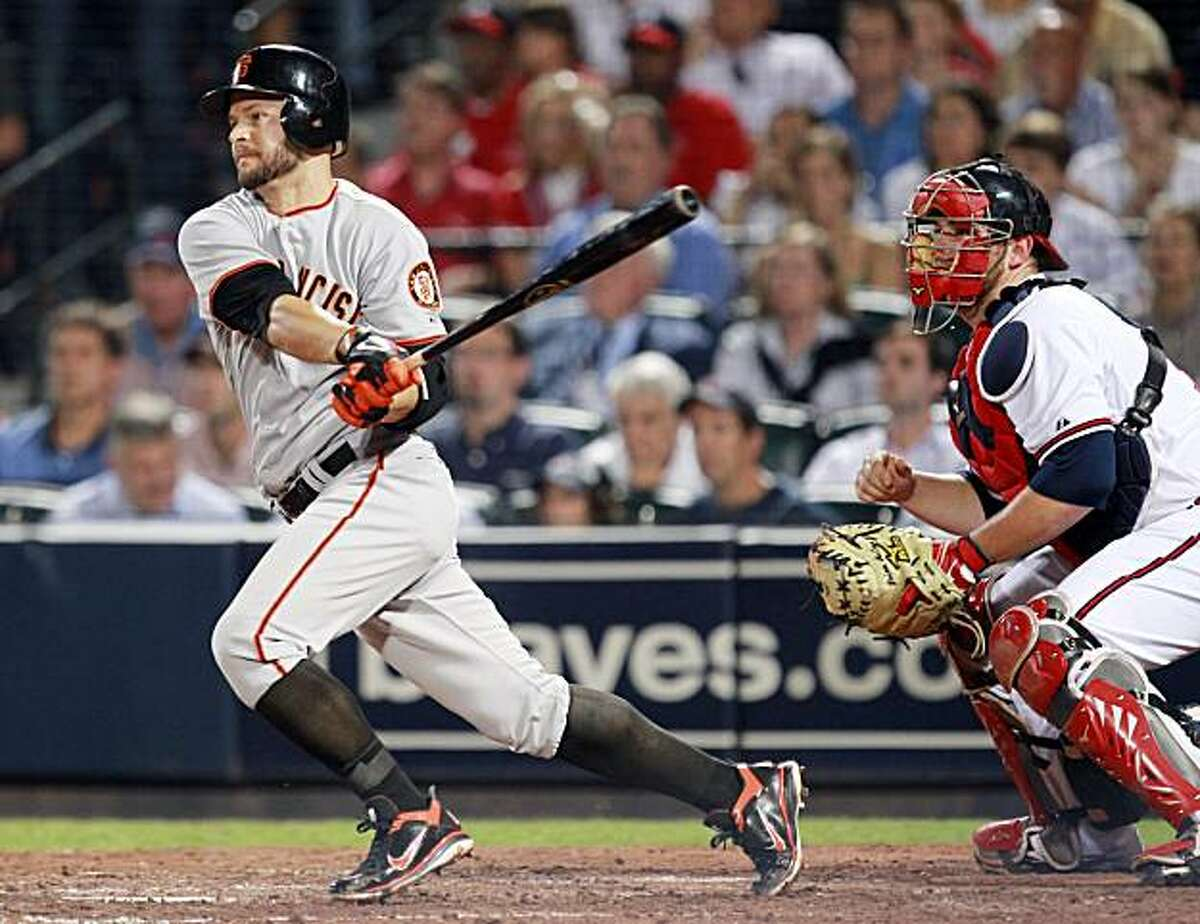 San Francisco Giants' Cody Ross drives in the go-ahead run with a base hit as Atlanta Braves catcher Brian McCann (16) looks on in the seventh inning of Game 4 of baseball's National League Division Series on Monday, Oct. 11, 2010, in Atlanta. San Francisco won 3-2.