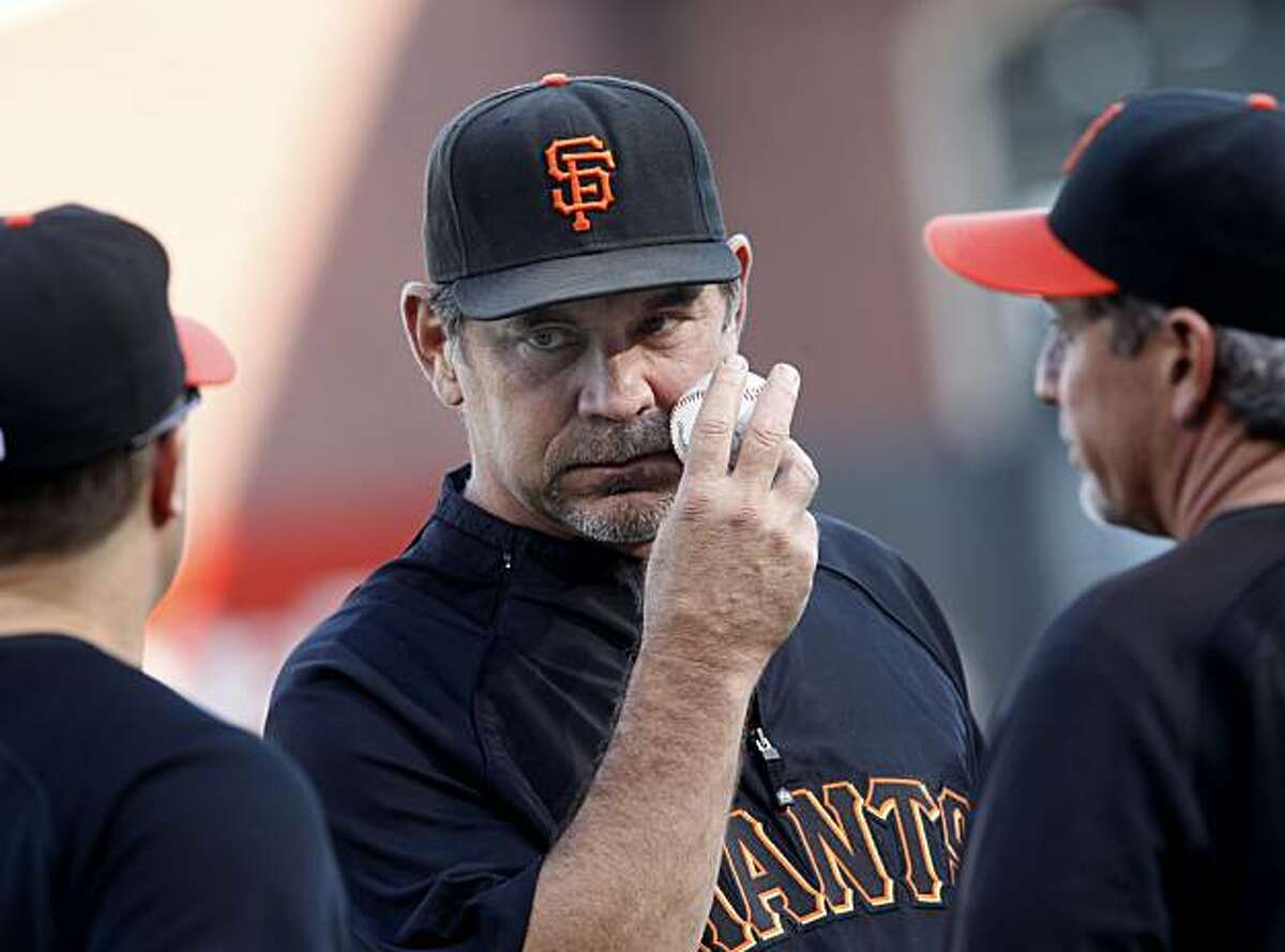 Manager Bruce Bochy talks to his coaches before the Giants' workout Monday at AT&T Park.