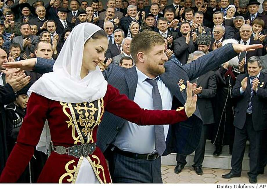 ** ADVANCE FOR SUNDAY, MARCH 1 ** This March 2, 2007 photo released by NewsTeam shows Ramzan Kadyrov, Chechnya's president dancing with a Chechen girl dressed in a national costume in Grozny, Russia. With money from Moscow, Chechen President Ramzan Kadyrov is rebuilding Grozny at a frenetic pace. Some in Russia say Kadyrov's attempt to create an Islamic society violates the Russian constitution, which guarantees equal rights for women and a separation of church and state. But the Kremlin has given him its staunch backing, seeing him as the key to keeping the separatists in check, and that has allowed him to impose his will. (AP Photo/NewsTeam, Dmitry Nikiforov) ** NO ONLN ** NO IONLN ** Photo: Dmitry Nikiforov, AP