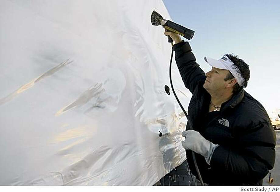 **APN ADVANCE FOR SUNDAY MARCH 1** Fast Wrap USA co-founder Mike Enos heats up a plastic coating over stacks of pipes on a job site in Reno, Nev., Monday, Dec. 1, 2008. Enos says use of the plastic protectant product is growing beyond marinas,  to disaster zones, construction sites and basic backyard uses.  (AP Photo/Scott Sady) Photo: Scott Sady, AP