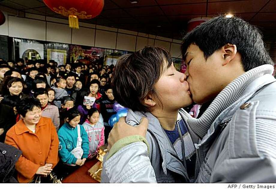 A Chinese couple competes in a kissing contest to mark Valentine's Day in Hefei, central China's Anhui province on Valentine's Day February 14, 2009. Businesses in China are cashing in on the growing popularity of western traditions such as Valentine's Day, selling products with a theme of love, such as flowers and chocolates, is proving to be lucrative. Photo: AFP, Getty Images