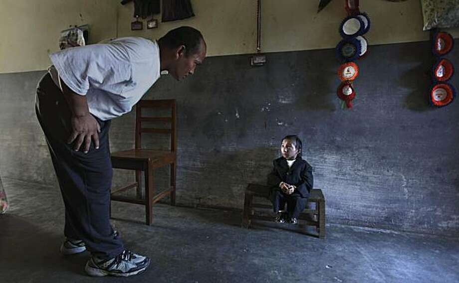 Nepal's Khagendra Thapa Magar sits on a small stool inside his home as his father, Rup Bahadur Magar, speaks to him on the eve of his eighteenth birthday in Pokhara, some 200 kilometers (124 miles) from Katmandu, Nepal, Wednesday, Oct. 13, 2010. Thapa, who is 25.8 inches tall, (65.532 centimeters) according to the Guinness World Records Press Release,    is likely to be declared the shortest person in the world after officials from the Guinness World Records have flown to his hometown Pokhara in central Nepal to make final examinations. Photo: Altaf Qadri, Associated Press