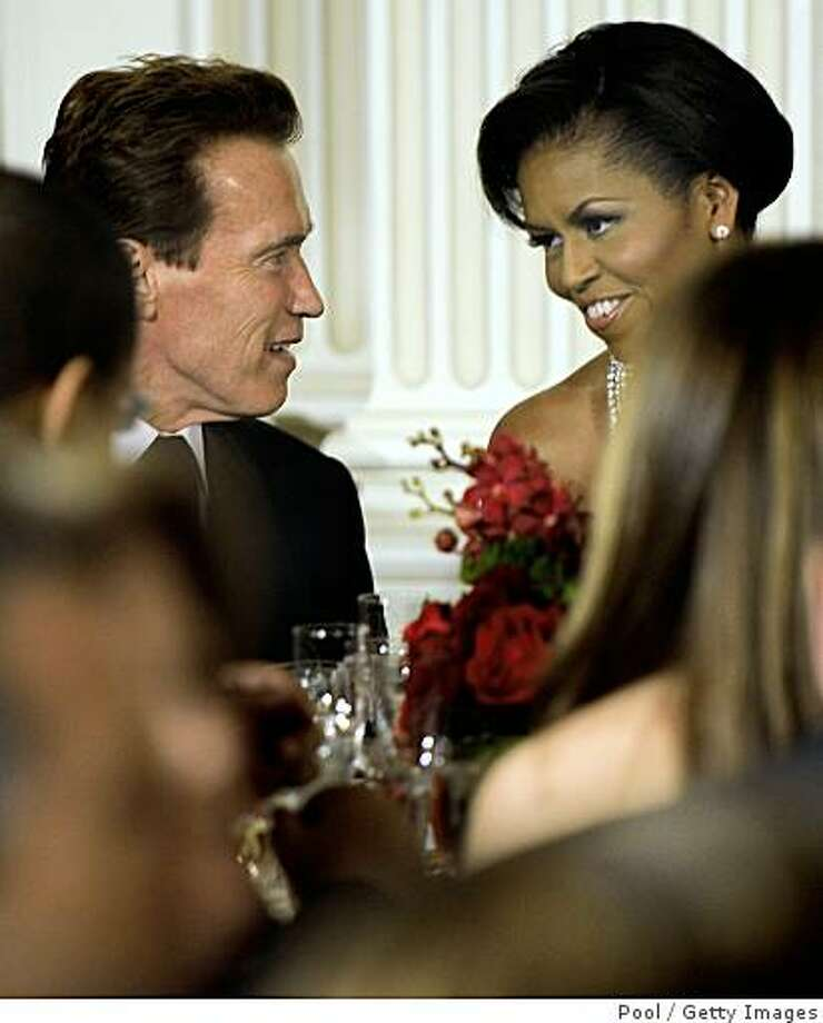 California Governor Arnold Schwarzenegger sits next to first Lady Michelle Obama at a black-tie dinner at the White House on Feb. 22, 2009 in Washington, D.C. The Obamas gave their first formal White House dinner as hosts to the National Governors Association, which was been holding their 2009 winter meeting discussing Obama's stimulus program, health care, infrastructure and education. Photo: Pool, Getty Images