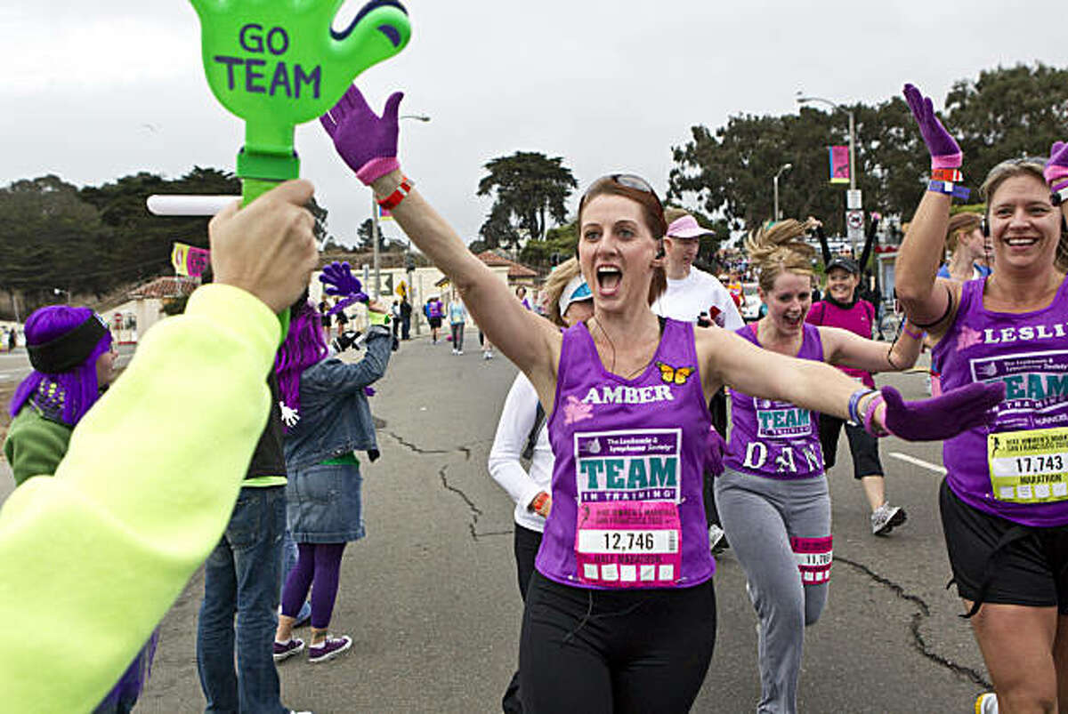 Runners get a high five while running along Marina Boulevard during the Nike Women's Marathon in San Francisco, Calif., on Sunday, October 17, 2010.
