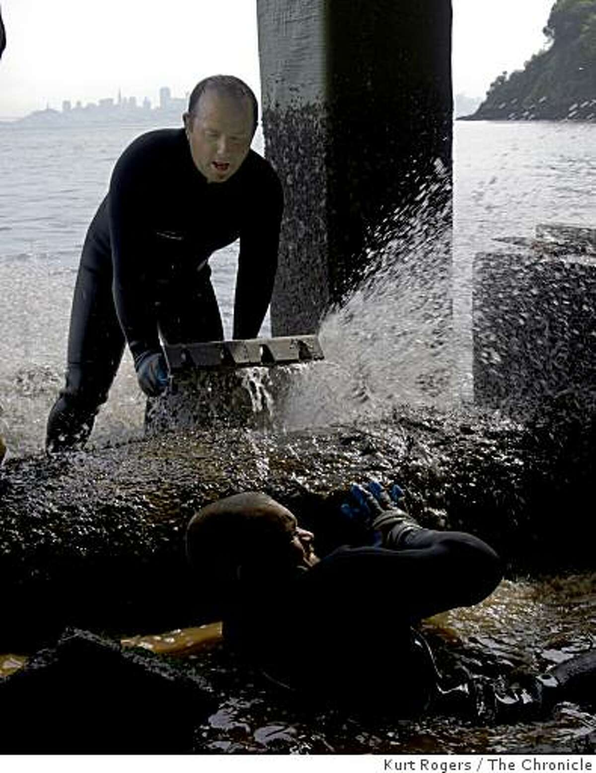 Tim Gulley (top) and Dallas Leighton, who work for Maggiora-Gailotti, try to fit a collar around the pipe thathas leaked thousands of gallons of treated sewage water into the bay at the Sausalito-Marin City Sanitary District Fort Baker treatment plant on Feb. 18, 2009 in Sausalito, Calif.