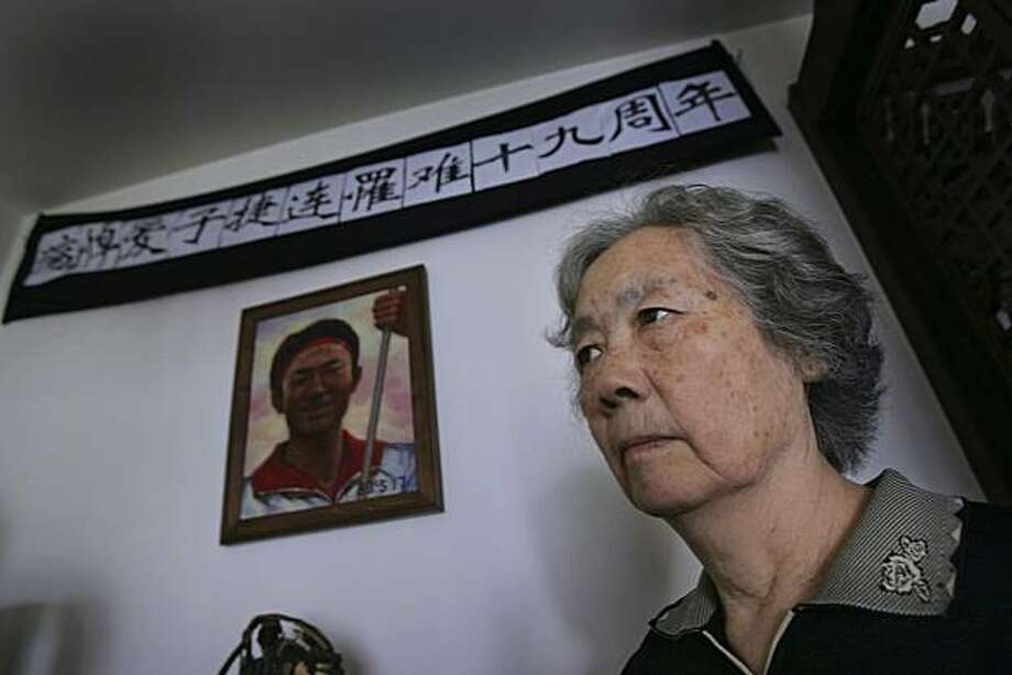 FILE - In this Juen 4, 2008 file photo, Ding Zilin, co-founder of the Tiananmen Mothers, a group representing families of those who died in the 1989 crackdown on pro-democracy demonstrations, stands in front of a shrine to her son, Jiang Jielian, who diedat 17, at her apartment in Beijing, marking the 19th anniversary of the military assault in Tiananmen Square. In the week after Liu Xiaobo won for his decades of promoting democratic change in China, dozens of people who openly agreed with his views saythey have been detained, roughed up, harassed or kept from leaving their homes. The latest appears to be a woman who Liu has said should win the prize: Ding Zilin, who has fought for years for China's government to recognize the hundreds killed in the m Photo: Greg Baker, AP