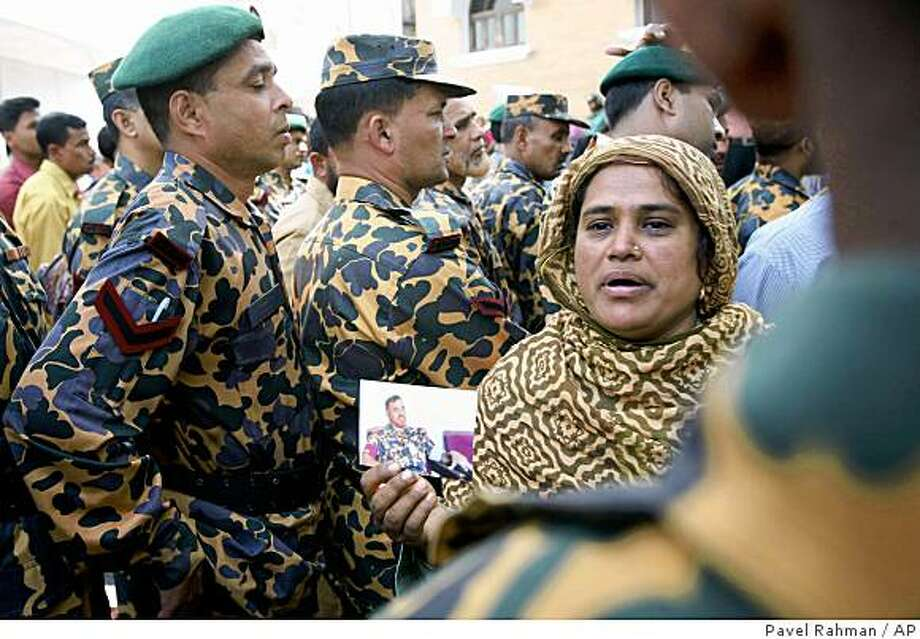 The wife of a missing Bangladeshi border guard holds his photo as she tries to gather information about him from those guards at their headquarters in Dhaka, Bangladesh, Sunday, March 1, 2009. Hundreds of Bangladeshi border guards started reporting back to their headquarters Sunday, two days after a bloody mutiny left at least 76 people dead and 72 others missing. The Home Ministry gave guards across the country a 24-hour ultimatum Saturday to return to their posts or report to a police station or face disciplinary action. (AP Photo/Pavel Rahman) Photo: Pavel Rahman, AP