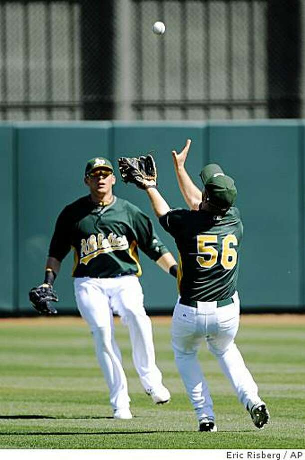 Oakland Athletics shortstop Cliff Pennigton, right, catches a fly ball hit by the Cleveland Indians Matt LaPorta as A's center fielder Ryan Sweeney, left, looks on during the second inning of their spring training baseball game in Phoenix, Saturday, Feb. 28, 2009. (AP Photo/Eric Risberg) Photo: Eric Risberg, AP