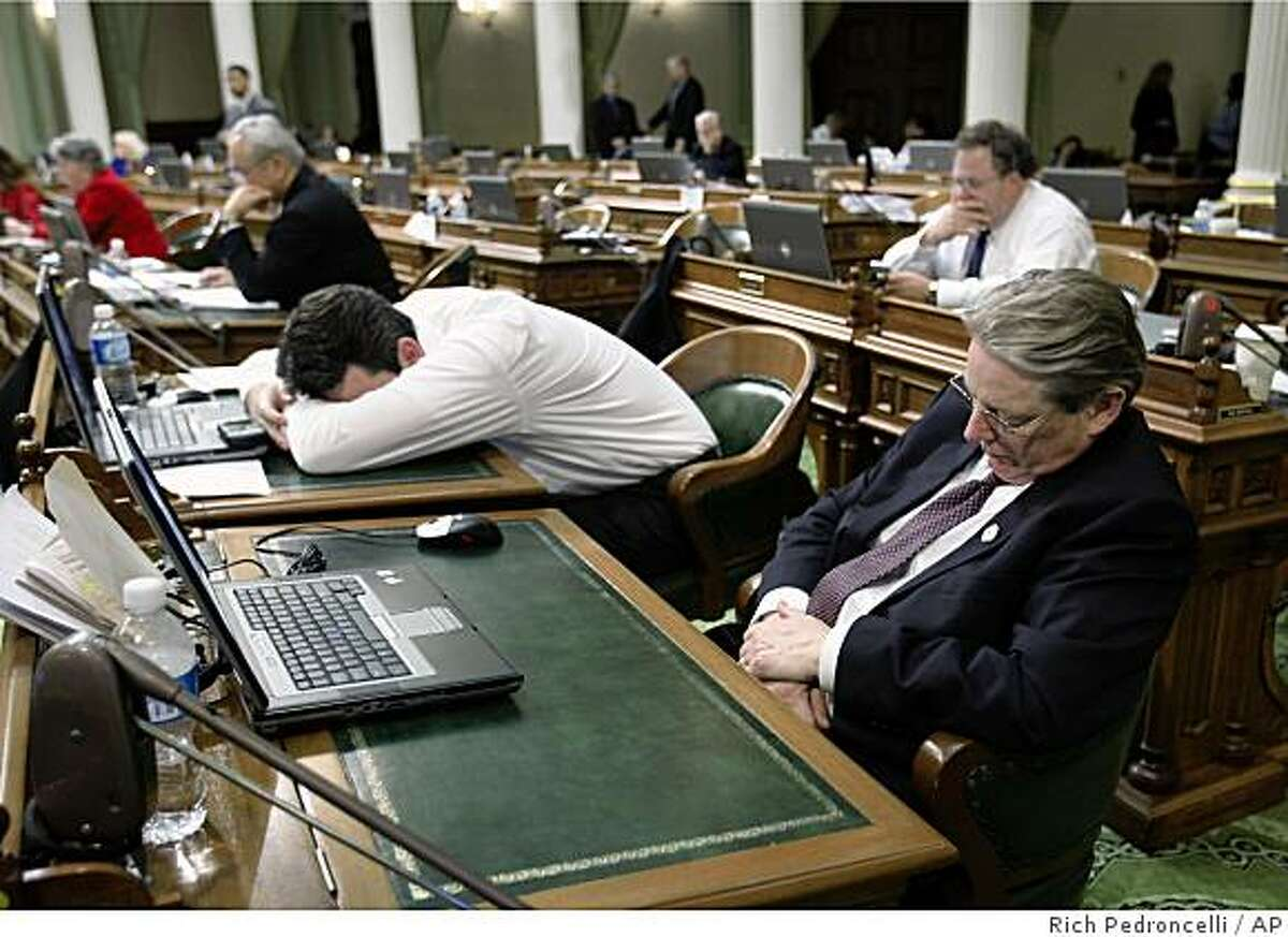 Assembly members Hector De La Torre, D-South Gate, left, and Bill Monning, D-Monterey, right, sleep at their desk during an all-night lock down of the Assembly at the Capitol in Sacramento, Calif., Sunday, Feb. 15, 2009. In an effort to get a budget deal, Assembly Speaker Karen Bass, D-Los Angeles, locked down her chamber about 3:30 a.m., forcing lawmakers to remain. (AP Photo/Rich Pedroncelli)