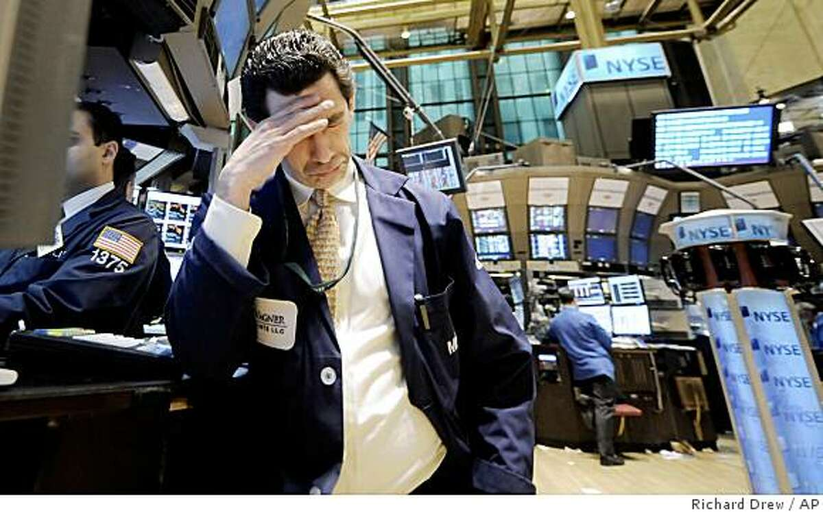 Specialist Peter Mazza works at his post on the floor of the New York Stock Exchange, Monday, Feb. 23, 2009. Investors unable to extinguish their worries about a recession that has no end in sight dumped stocks again Monday. The Dow Jones industrial average tumbled 251 points to its lowest close since Oct. 28, 1997, while the Standard & Poor's 500 index logged its lowest finish since April 11, 1997. (AP Photo/Richard Drew)