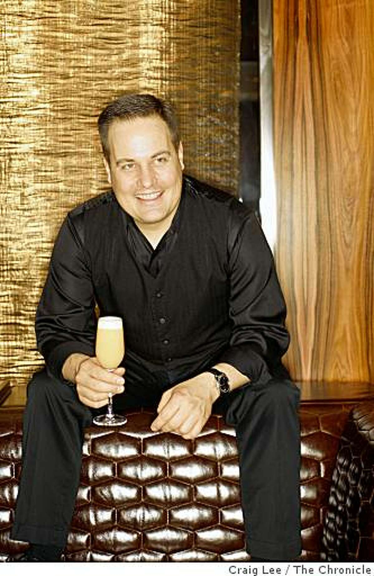 Marco Dionysos, bar manager at Clock Bar with his drink he created called English Breakfast in San Francisco, Calif., on February 18, 2009. Behind him is a curtain made of gold.