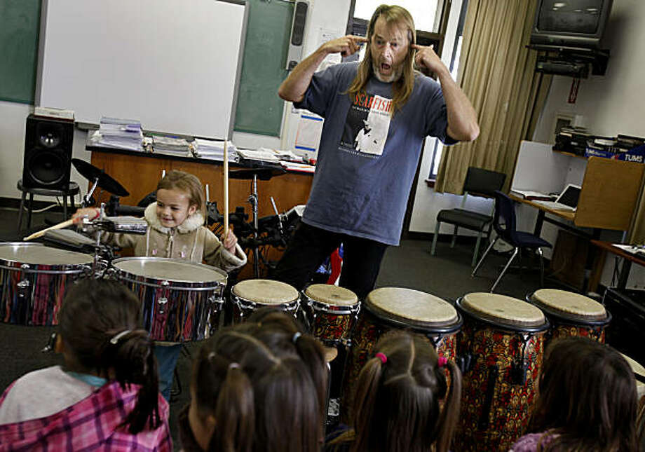 Kevin Wells clowns for the kids as a student in the local kindergarten class tries out some drums in the music room at Round Valley High School. Kevin Wells is known to Bay Area music fans as a rock drummer for Pablo Cruise and Huey Lewis and the News.  He has also written a number of hit songs, but now his passion for teaching children has caused him to go bankrupt in Covelo, Calif., where he and his wife Ronnelle keep dozens of injured, rescued horses and wolfdogs Wednesday September 22, 2010. Photo: Brant Ward, The Chronicle