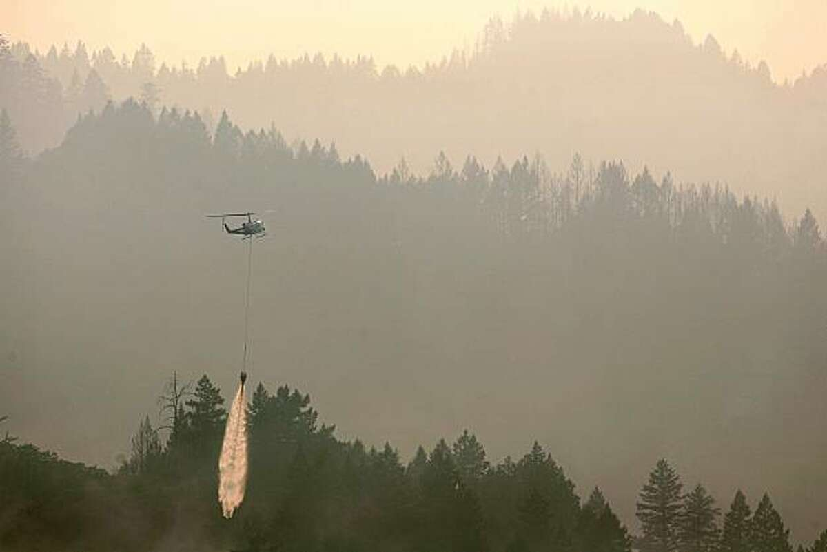 A water dropping helicopter drops on a hot spot on the Orr Fire, near Ukiah, Calif., Wednesday July 9, 2008. The fire is part of the Mendocino Lightning Complex, 127 fires that were sparked by lightning nearly three weeks ago. The fires have burned an estimated 51,000 acres. The fire is one of hundreds burning throughout California.