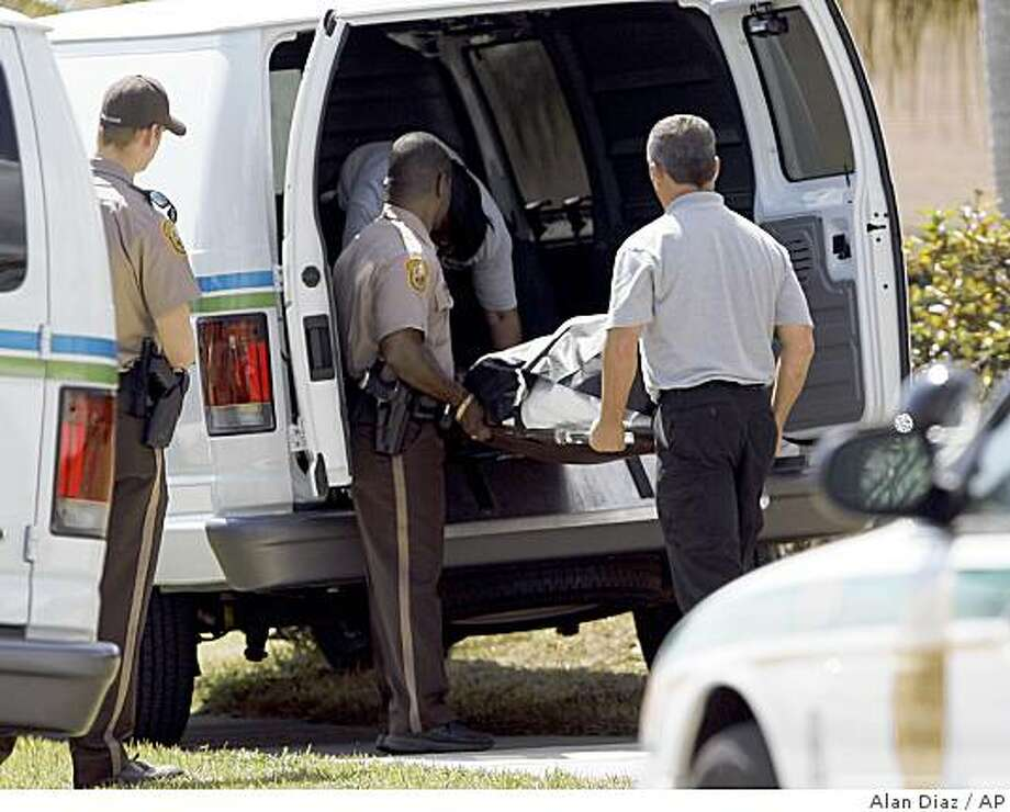 Medical examiners place one of four bodies inside a Medical Examiners van in Miami, after an early morning shooting Wednesday, Feb. 25, 2009. A 53-year-old man fatally shot his wife and two daughters Wednesday before turning the gun on himself, and a 16-year-old son who survived the attack managed to call police on a cordless phone as he fled, police said. (AP Photo/Alan Diaz) Photo: Alan Diaz, AP