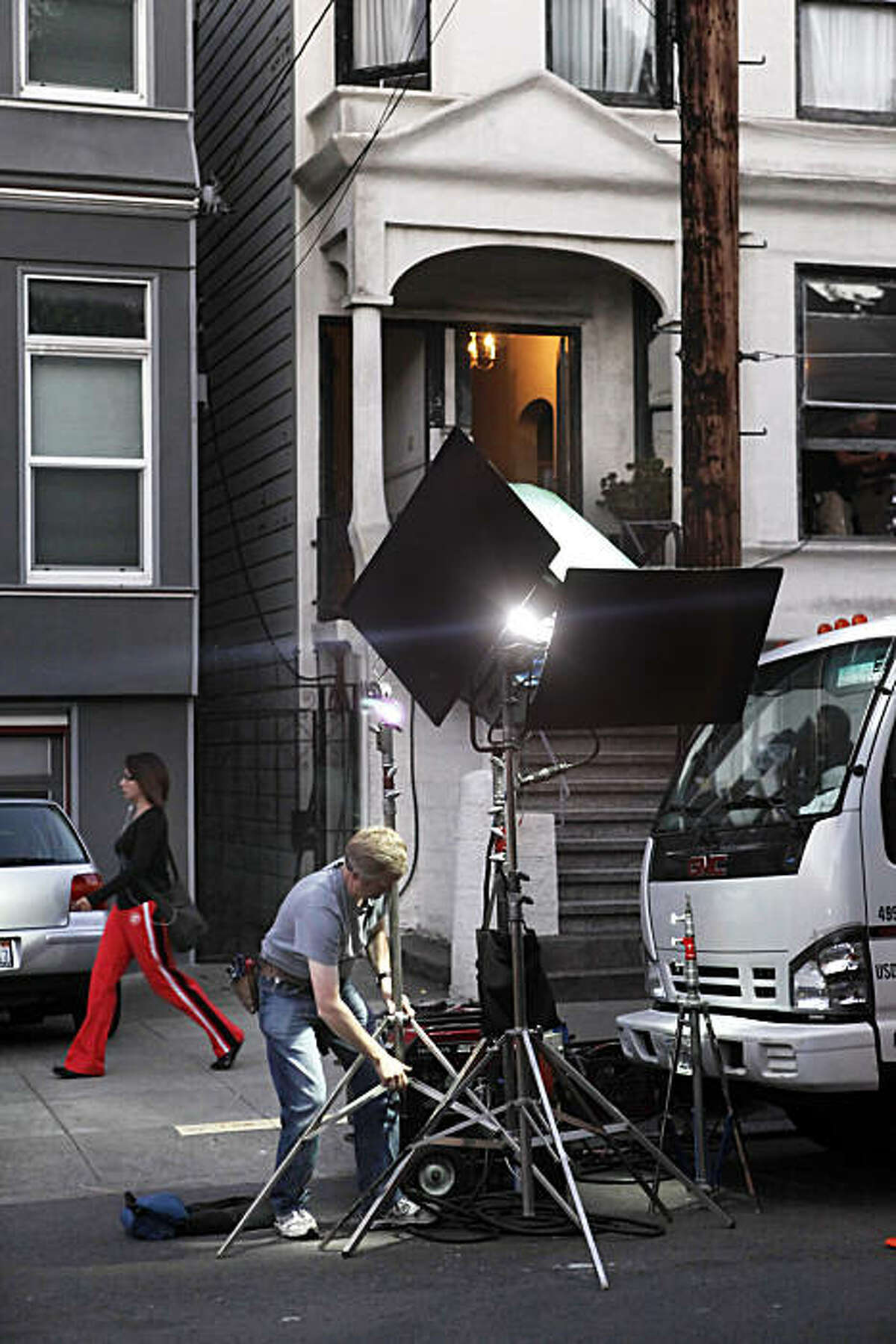 Brook Johnson, adjusting light, is a member of IA Local 16 and is working as a best boy electric on a film set on Cole Street in San Francisco, Calif., on Wednesday, October 13, 2010. The project, a Japanese TV series, was doing a quick shoot in one of the houses, but even this quick shoot was a boost to local merchants, union drivers, electricians, restaurants and hotels as money from the production always goes into the local economy.