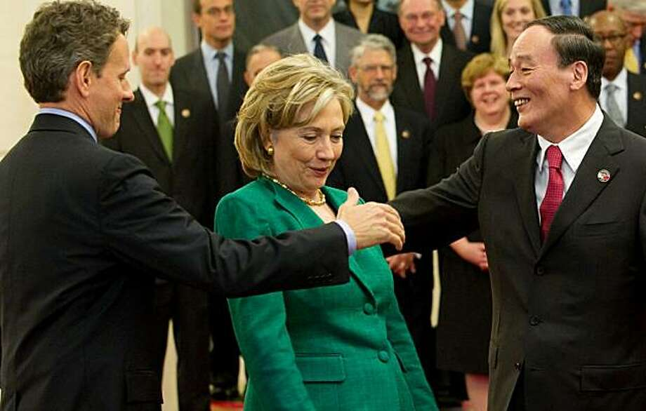 Chinese Vice-Premier Wang Qishan (R) tries to shake hands with US Secretary of Treasury Timothy Geithner (L) around Secretary of State Hillary Clinton (C) prior to a family photo with US and Chinese officials at the Great Hall of the People in Beijing, May 24, 2010, during the start of the second round of the US-China Strategic & Economic Dialogue. The United States and China opened annual high-level strategic talks, with the US trying to persuade Beijing to back tough action against North Korea over thesinking of a Seoul warship.  TOPSHOTS Photo: Saul Loeb, AFP/Getty Images