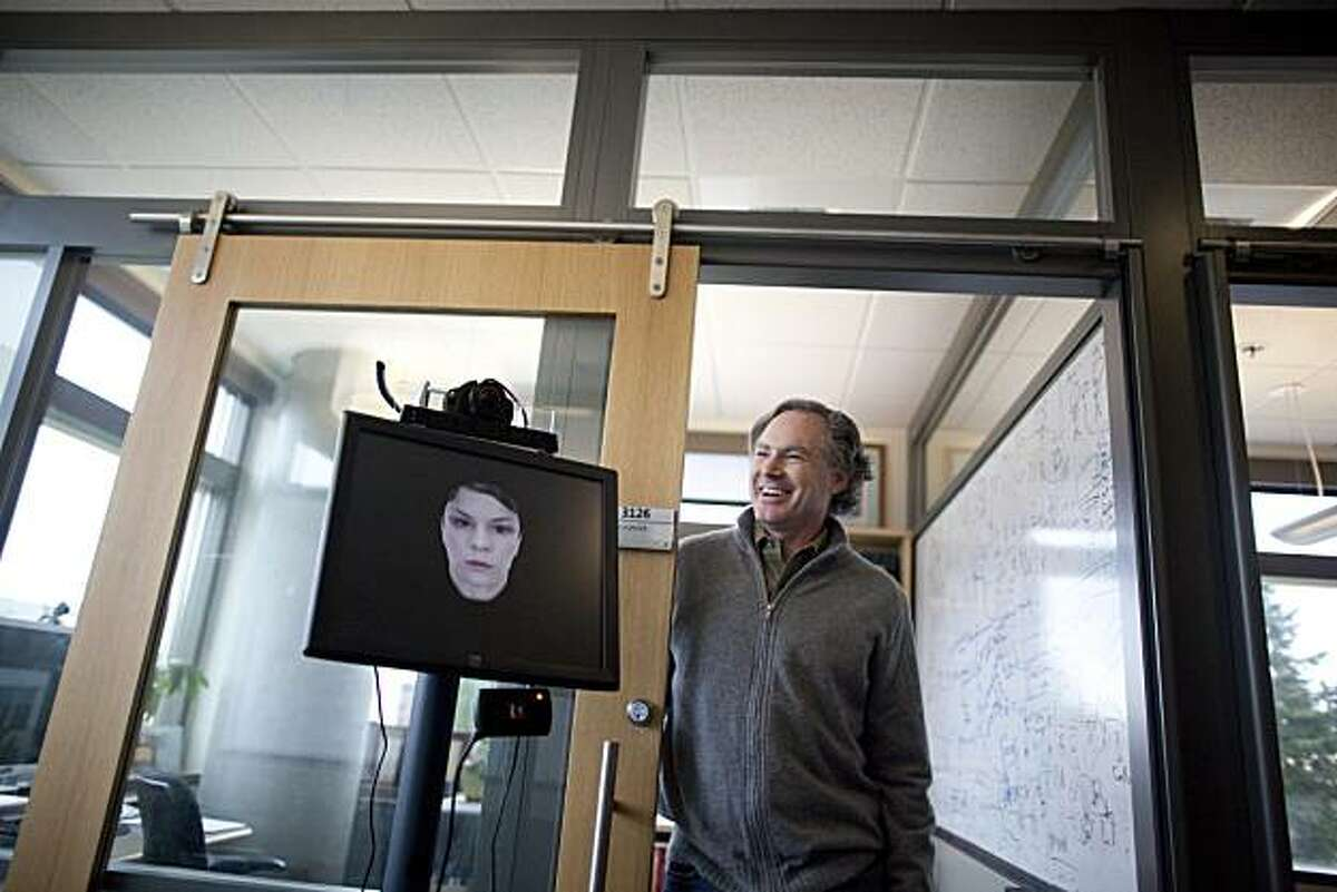 Eric Horowitz, a distinguished scientist at Microsoft Research, stands with his Personal Assistant for Scheduling system, PASS, an artificial intelligence virtual receptionist, at his office on the Microsoft campus in Redmond, Wash.