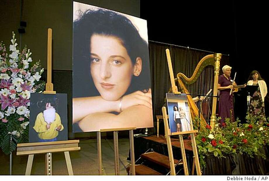 *** FILE *** Photos of Chandra Levy are on display as musicians, right, stand by at the memorial service for Levy in this Tuesday, May 28, 2002 file photo taken at the Modesto Centre Plaza in Modesto, Calif.  Media reports Saturday Feb. 21, 2009 in Washington and California say that an arrest may be close in the slaying of the former federal intern whose disappearance ended Gary Condit's congressional career. The warrant is expected to be for a prison inmate convicted of attacking two female joggers in the same Washington park where Levy's remains were found. (AP Photo/Debbie Noda, Pool, File) Photo: Debbie Noda, AP