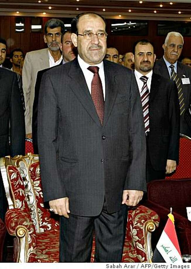 Iraqi Prime Minister Nuri al-Maliki stands during the national anthem prior to speaking at a conference about the country's economic climate in central Baghdad on February 25, 2009. Iraq, which sits on the world's third largest known petroleum reserves, wants to diversify its revenues in the light of the tumbling price of crude oil. AFP PHOTO/POOL/SABAH ARAR (Photo credit should read SABAH ARAR/AFP/Getty Images) Photo: Sabah Arar, AFP/Getty Images