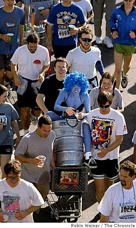 woman covered with blue paint rides on top of a shopping cart with keg of beer as her friends push her down Howard Street during the 88th annual Bay to Breakers in San Francisco. Photo: Robin Weiner, The Chronicle