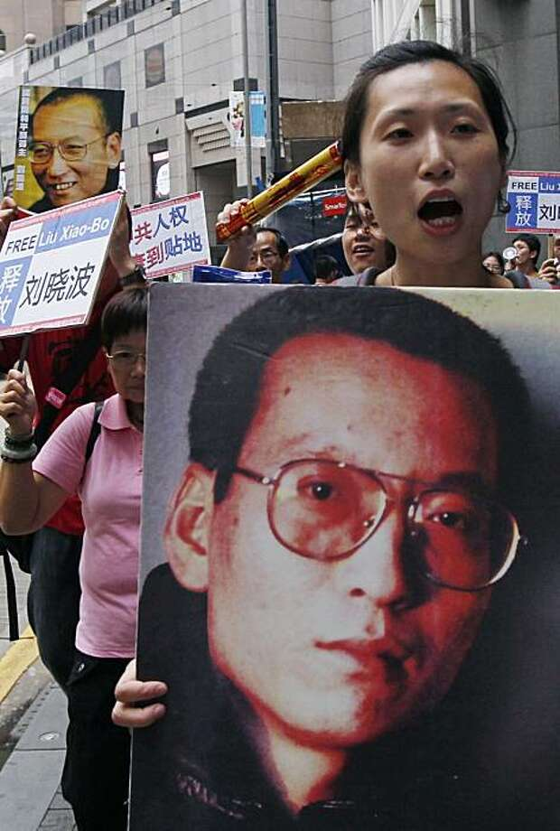 Pro-democracy protesters hold the picture of Chinese dissident Liu Xiaobo as they march to the China's Liaison Office in Hong Kong Sunday, Oct. 10, 2010. Awarding the Nobel Peace Prize to the imprisoned Liu sparked praise from Western governments, broughtcondemnation from Beijing and is exposing the difficulties fitting a powerful, authoritarian China into the international order. Photo: Kin Cheung, AP