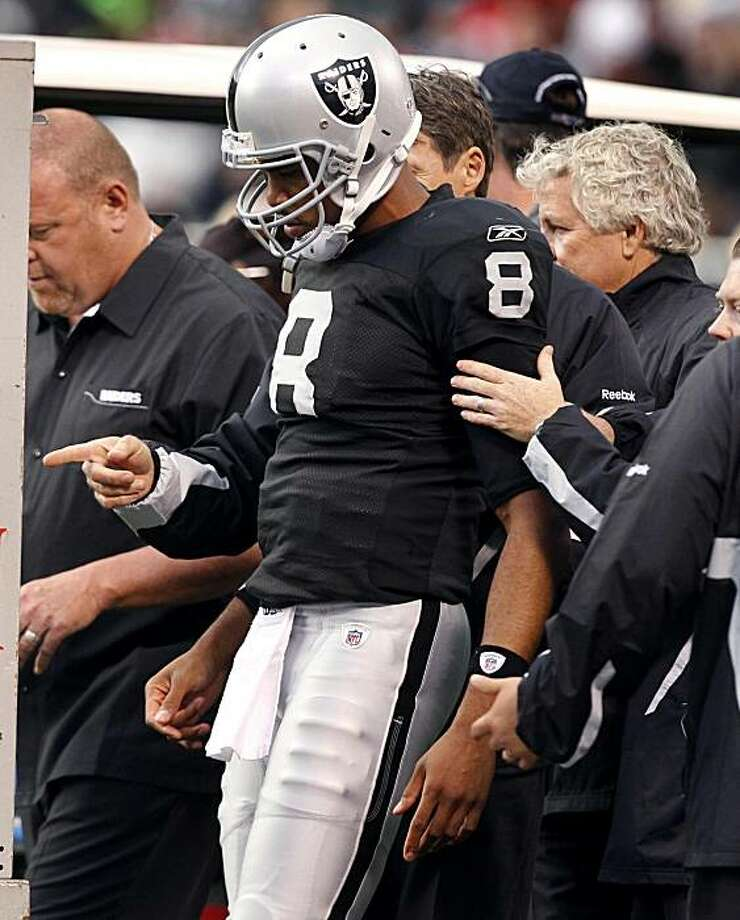 Raiders quarterback Jason Campbell is helped off the field after he left the game in the second quarter against the 49ers in Oakland on Saturday. Photo: Paul Chinn, The Chronicle