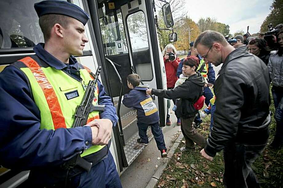 As a local policeman stands guard, family members from Kolontar village get into a bus to return their home village in front of their temporary home, the local sports hall of Ajka town about 140 km west of Budapest on  October 15, 2010. More than 700 citizens were evacuated from their home Kolontar on October 9 early morning when authorities feared a second flood of toxic sludge from a chemicals plant was likely after new cracks appeared in a dyke. Wave of toxic red mud swept through the small village onOctober 4, killing eight people and injuring scores more. Photo: Balint Porneczi, AFP/Getty Images