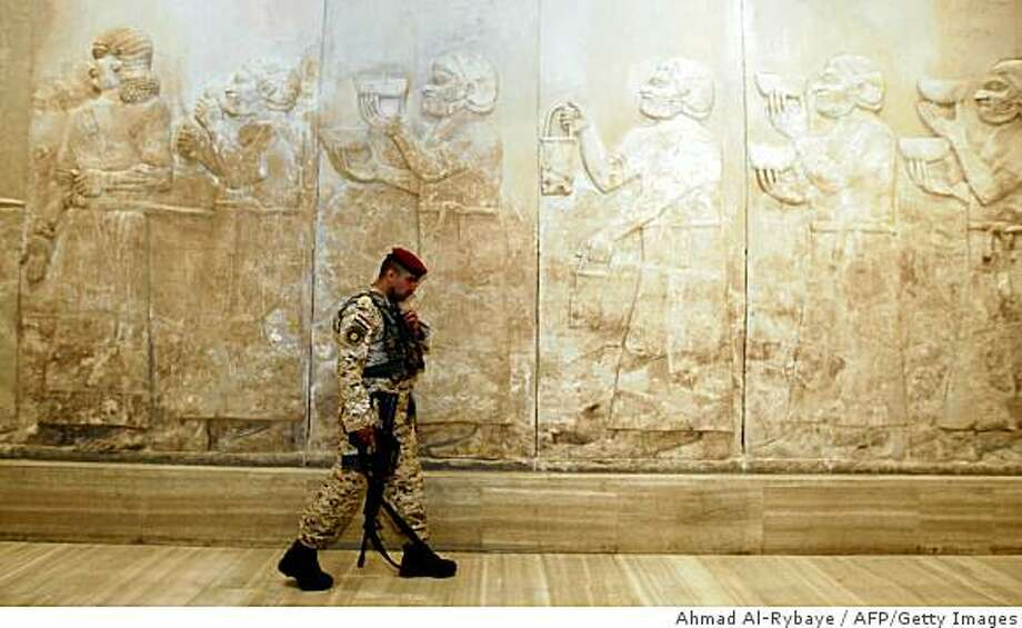 An Iraqi security officer walks through the Assyrian hall at the Iraqi Museum, on February 23, 2009. The Iraq Museum, the pride of the nation known as the cradle of civilization, reopened almost six years after its ancient treasures were looted in the chaotic aftermath of the US-led invasion.  AFP PHOTO / AHMAD AL-RUBAYE (Photo credit should read AHMAD AL-RUBAYE/AFP/Getty Images) Photo: Ahmad Al-Rybaye, AFP/Getty Images